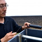 Dongqing Lin inspects monitoring equipment at ND Clay Co. Farm